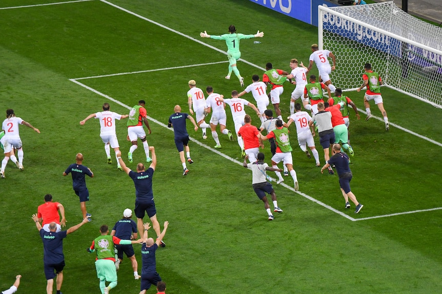The entire Switzerland team, including substitutes and some staff, chase after the goalkeeper