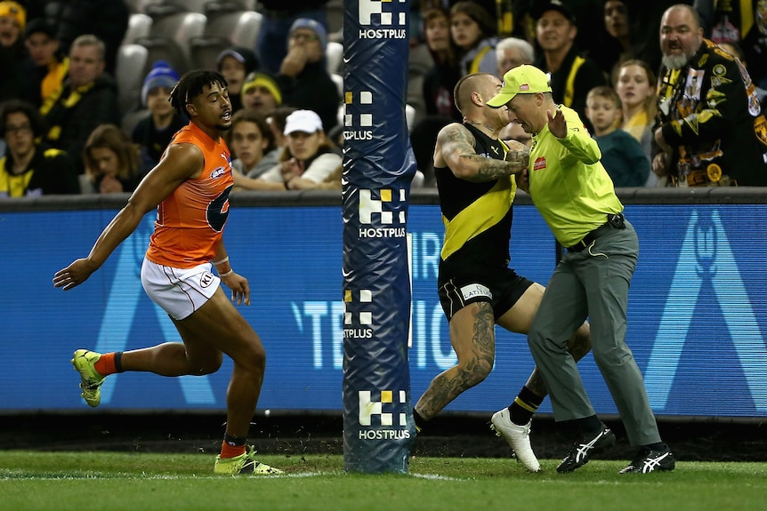 AFL player collides with the goal umpire during a match