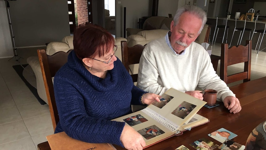A man and woman sit at a table looking through a photo album.