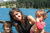 A smiling dark-haired woman holds two children in front of a scenic lake in New Zealand.