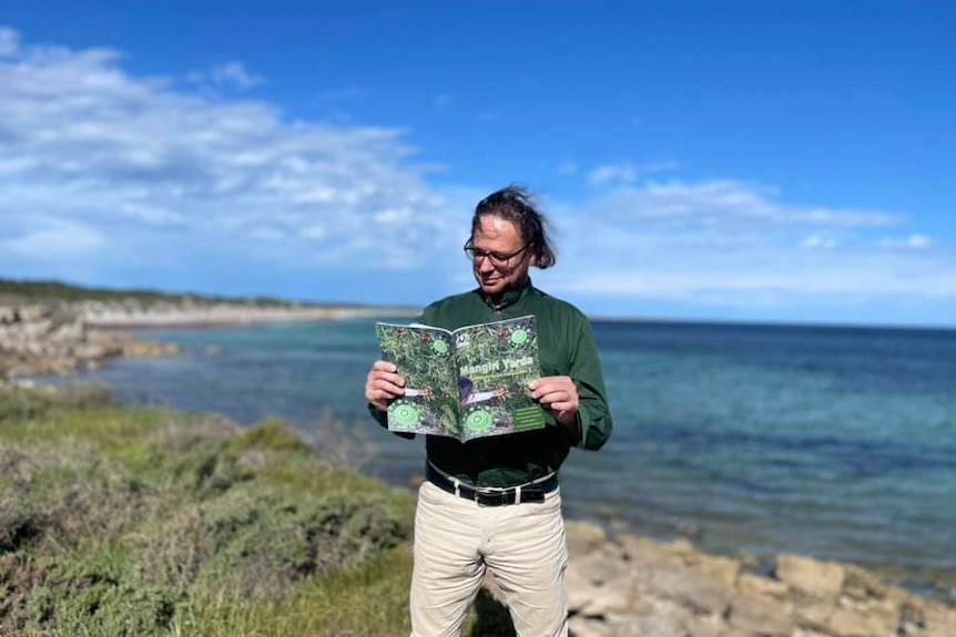 A man with messy hair standing on a clifftop with ocean behind him reading a large book.