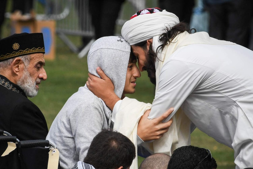 A man wearing a head dress puts his forehead against that of teenager Zaid Mustafa.