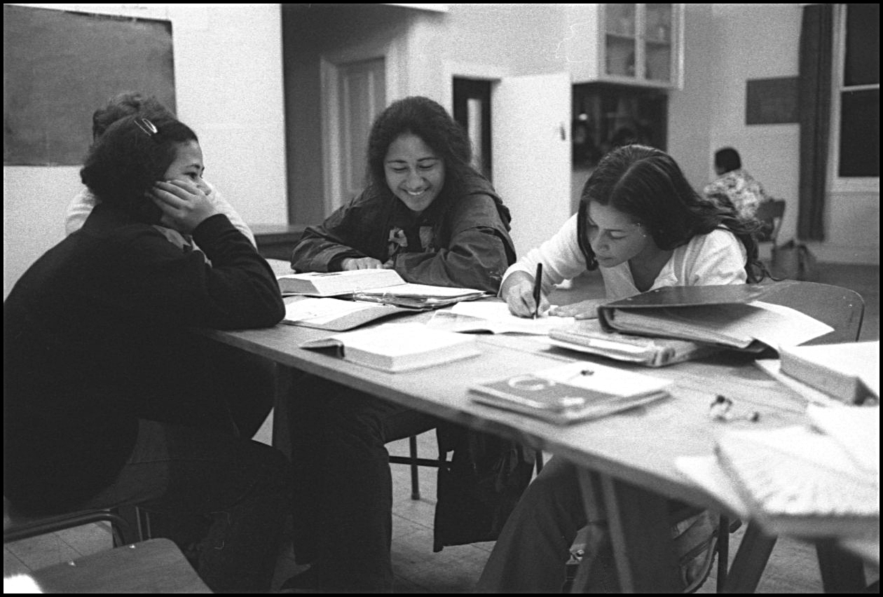 Four young women sit at a table working.