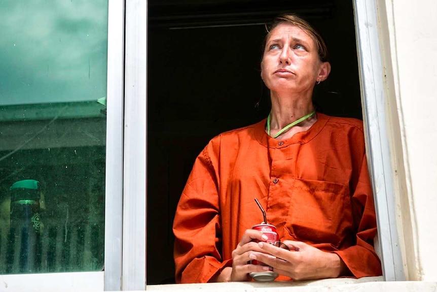 A woman in prison orange uniform looks solemn standing by a window