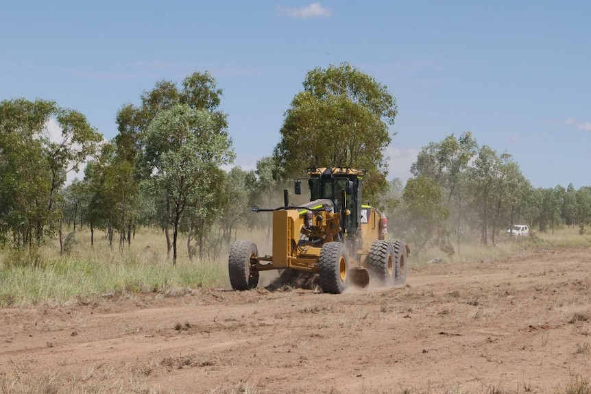 A grader doing preliminary work to the section of ground at Adani's Carmichael coal mine.