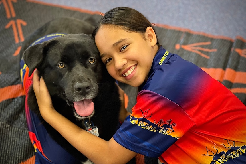 Therapy dog Sheekie and a student.