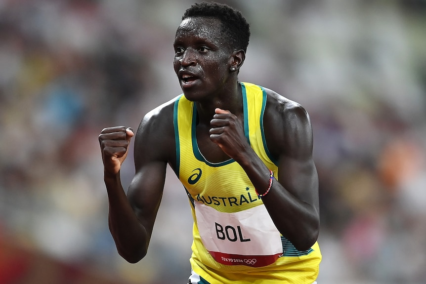 Peter Bol clenches his fists in a yellow Australia singlet.