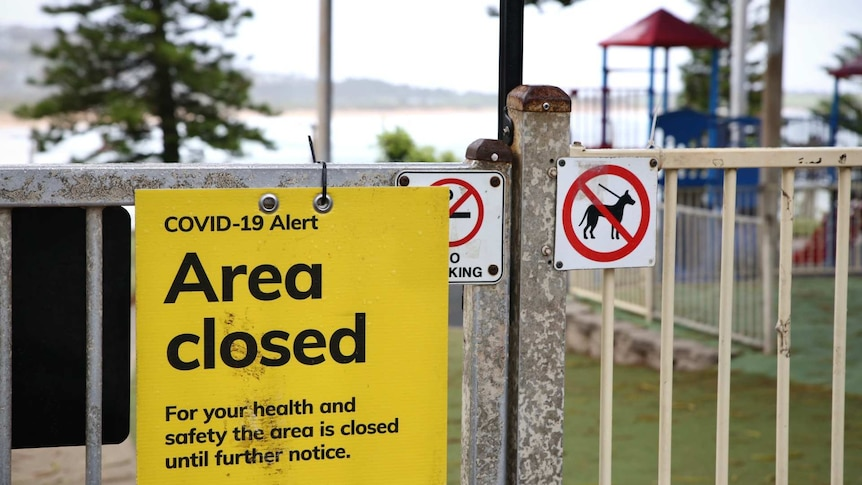 an area closed sign outside a beach playground