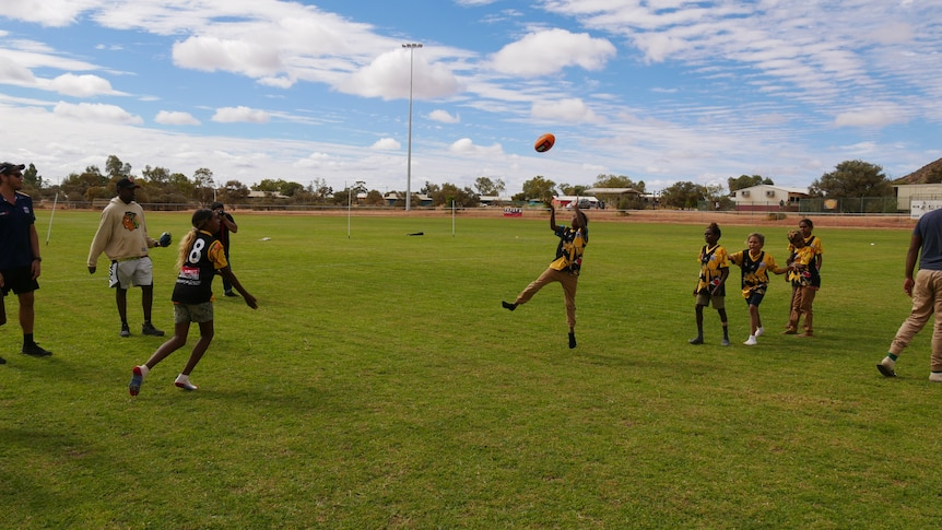 An Indigenous boy jumps in the air to catch an AFL ball, while other children and people watch.