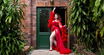 A woman strikes a pose in a doorway. She wears a red corset and briefs covered with a red translucent gown with furry cuffs.