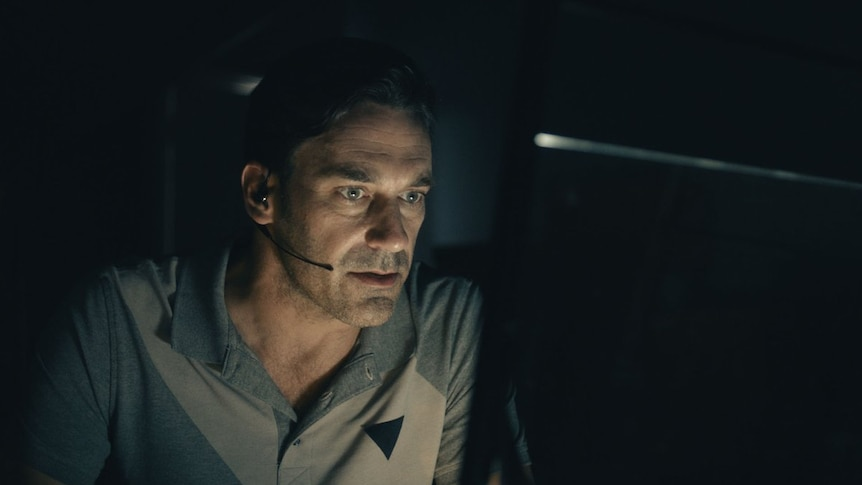 Jon Hamm sits in a dark room in front of a computer with a headset