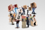 """An illustration shows several workers straining while holding boxes spelling out the words """"unfair work""""."""