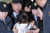 Choi Soon-sil, escorted by security officers and wearing a white jumpsuit and surgical mask, arrives for questioning.