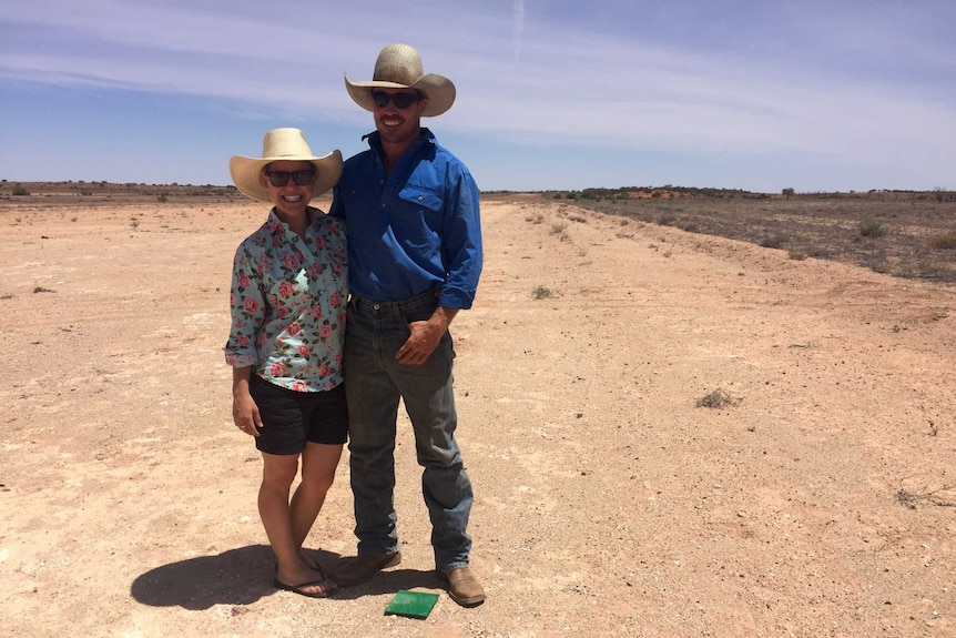 Emma and Fred Osman stand on the airstrip at a remote Queensland station near the NSW border.