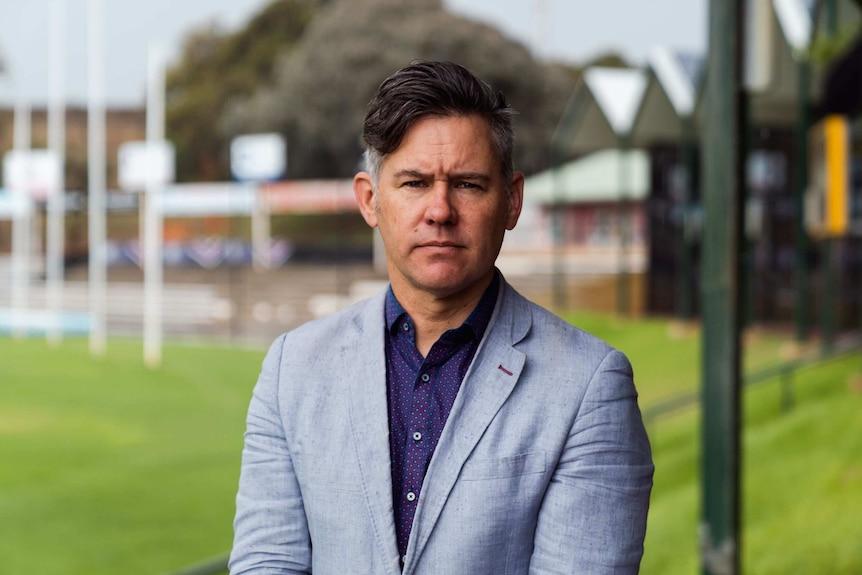 Man in suit stands in empty football stadium
