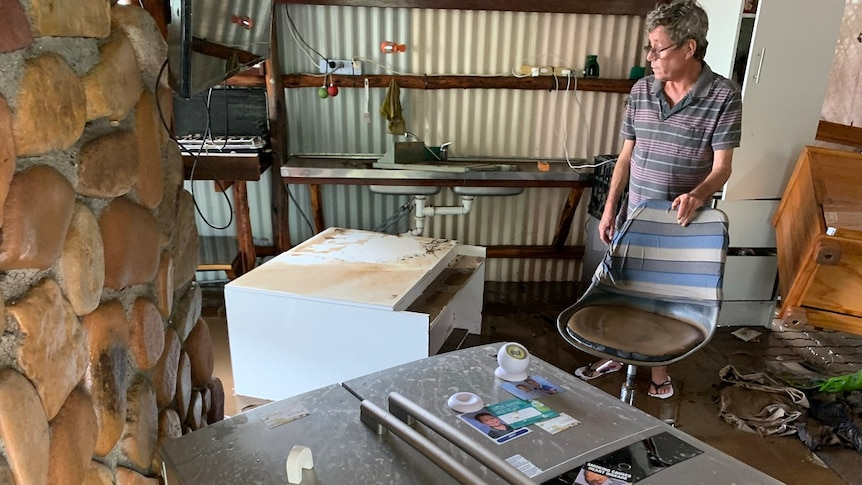 Clive Nesbitt looks at his belongings displaced and covered in mud, fridge on its side, cabinet and other furniture ruined.