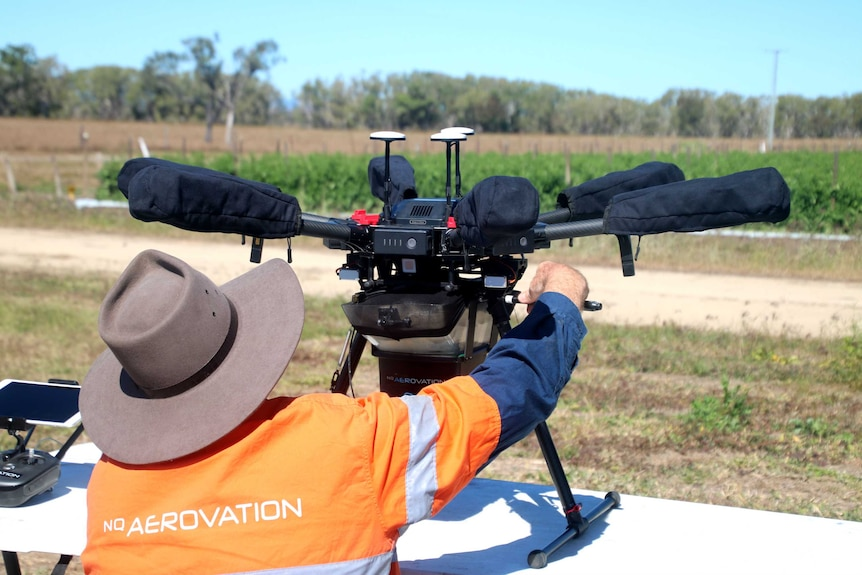 A man with a big hat is working on a drone with six propellers on a table.