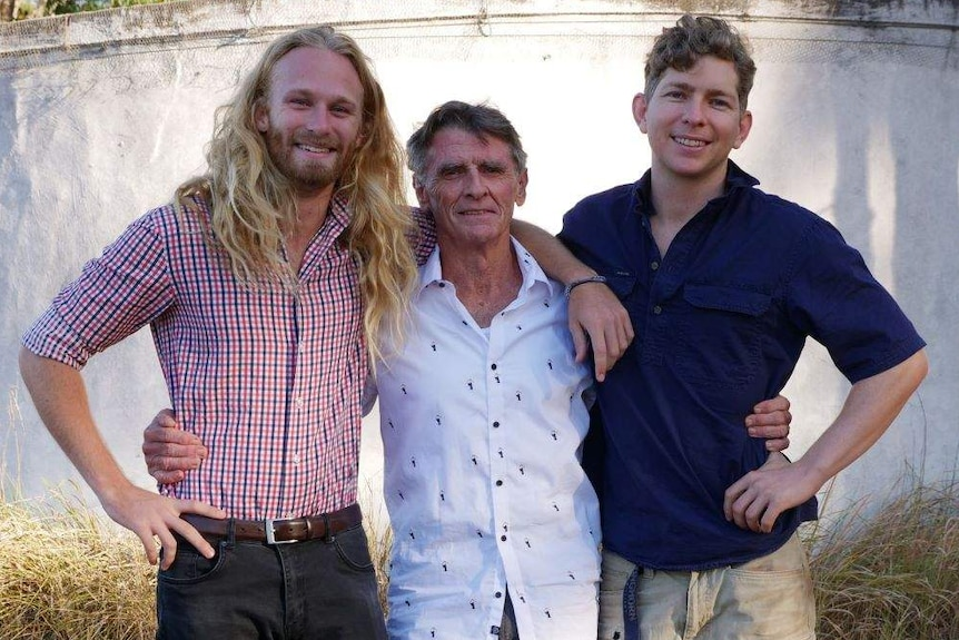 Three young man stand on either side of an older man with their arms around his shoulders.