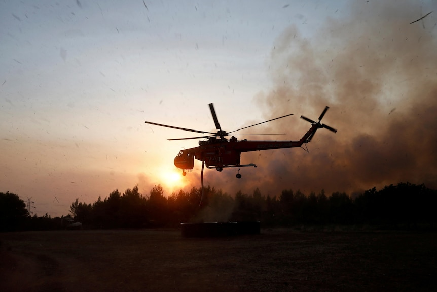 A silhouetted helicopter flies above the tree line at dusk with a fire burning behind it in the distance