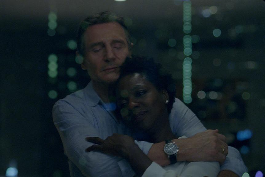 Colour still of Liam Neeson embracing Viola Davis in 2018 film Widows.