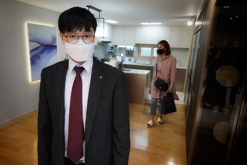 A young Korean man in a face mask and a suit stands in a kitchen while a woman walks past him