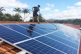 A worker from Katherine Solar NT cleans panels on a roof.
