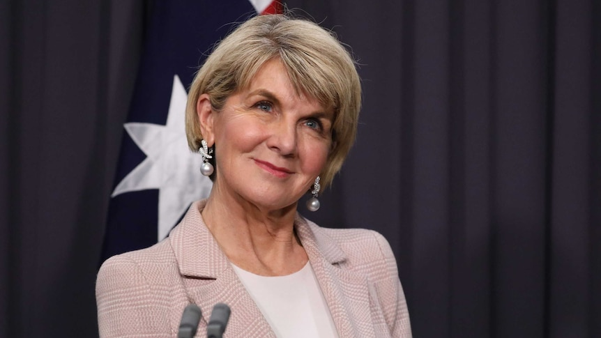 Bishop is smiling in front of an Australian flag.