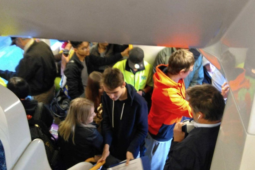 A train carriage full of people with standing room only, people squashed in next to each other.