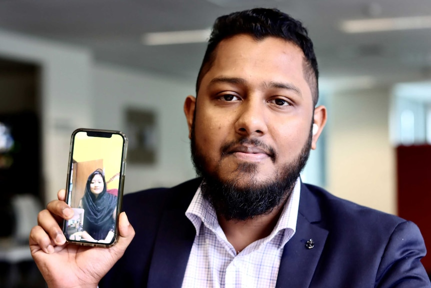 A Bangladeshi man wearing a suit looks inot the camera holding his phone which shows his wife on a video call