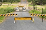'Road closed' signs and concrete blocks on a rural road.