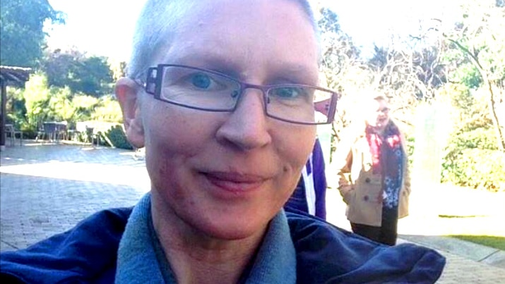 A woman with short hair and glasses looks at the camera, park in background.