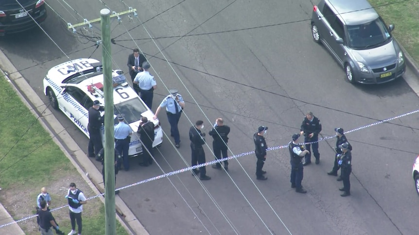 aerial vision of dozens of police officers standing in a street