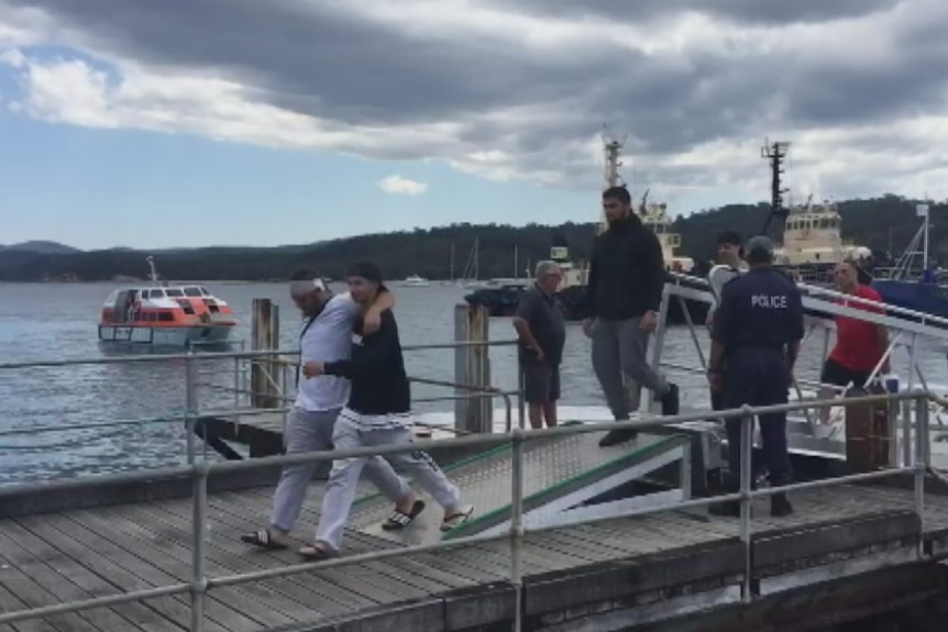 A man with a bandaged head leans on another man as they walk on a wharf