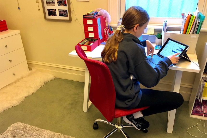 A girl looking at a tablet computer on a desk at her home.