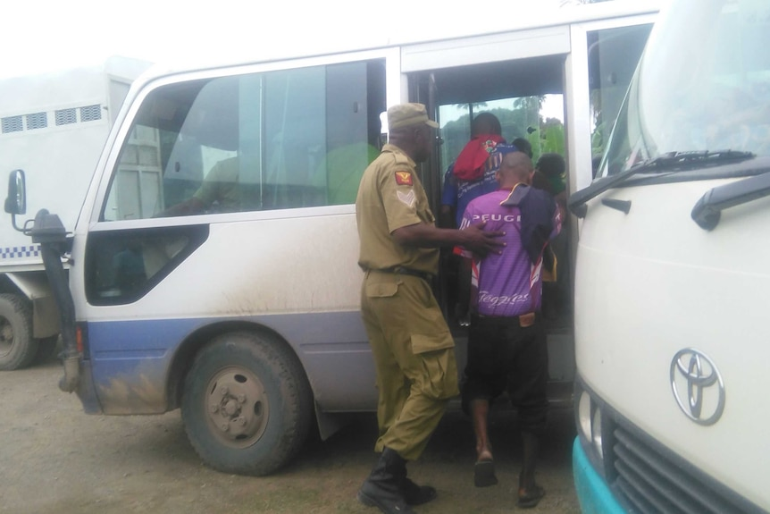 Correctional Service officers escorting some of the 99 accused onto a bus to take them to remand,  23 March 2017