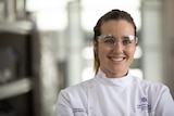 University of Queensland immunologist Dr Larisa Labzin, wearing goggles, smiles at the camera.