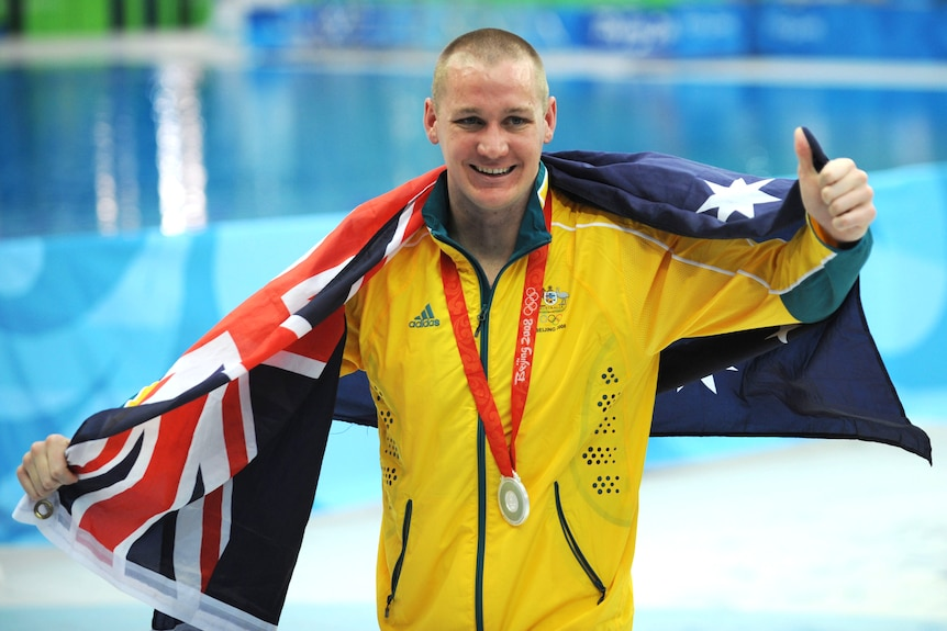 A man wearing and green and gold tracksuit and a silver medal around his neck holds an Australian flag over his shoulders.
