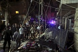 Residents inspect a damaged area caused by two explosions in Beirut's southern suburbs.