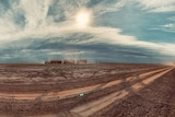 A dusty truck moves across the land