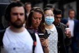 A woman wears a facebmask on a crowded street