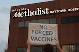 A protester holds a sign saying 'no  forced vaccines' in front of the Houston Methodist Baytown Hospital