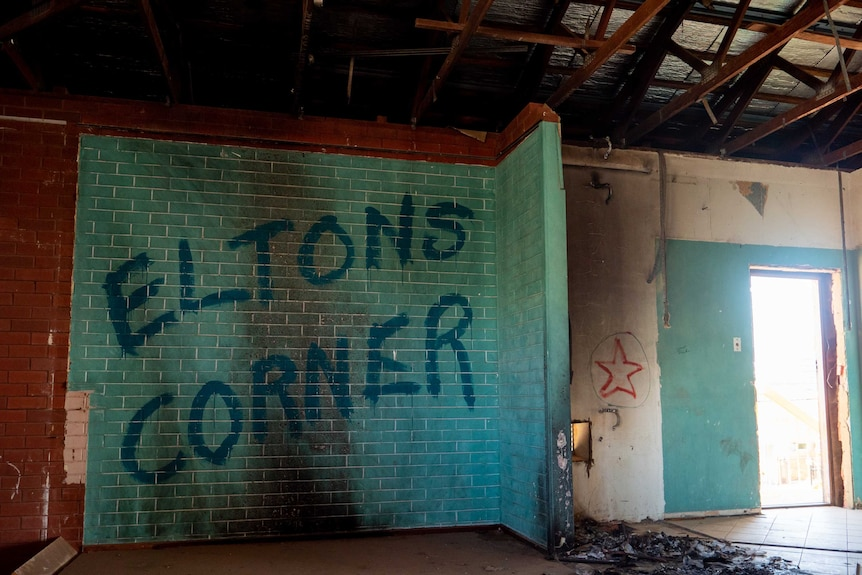 A blue brick wall is tagged 'Eltons Corner' and a pile of burnt debris lays on the ground.