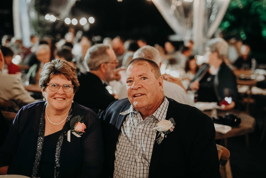 An older couple sitting together dressed up during a dinner event