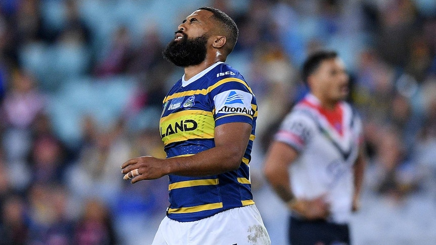Michael Jennings grimaces with his eyes closed playing for Parramatta against the Sydney Roosters.