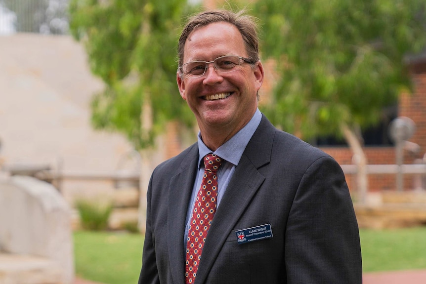A mid-shot of a smiling Guilford Grammar Preparatory School head Clark Wight in a suit and tie outdoors.