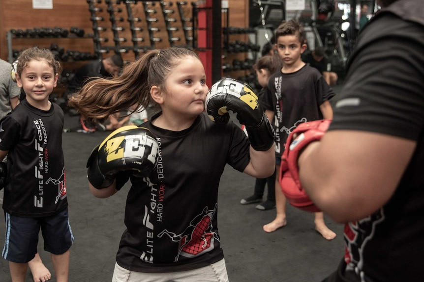 An action shot of a young girl throwing a punch at her trainer in a gym.
