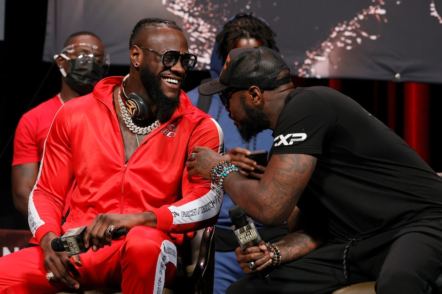 Deontay Wilder smiles at Malik Scott who leans into him