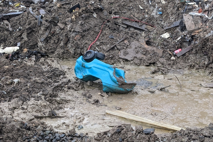 A blue broken child's plastic car lies in a puddle next to a hue pile of demolition waste.