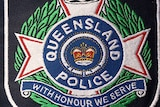 Queensland police logo on shirt sleeve.