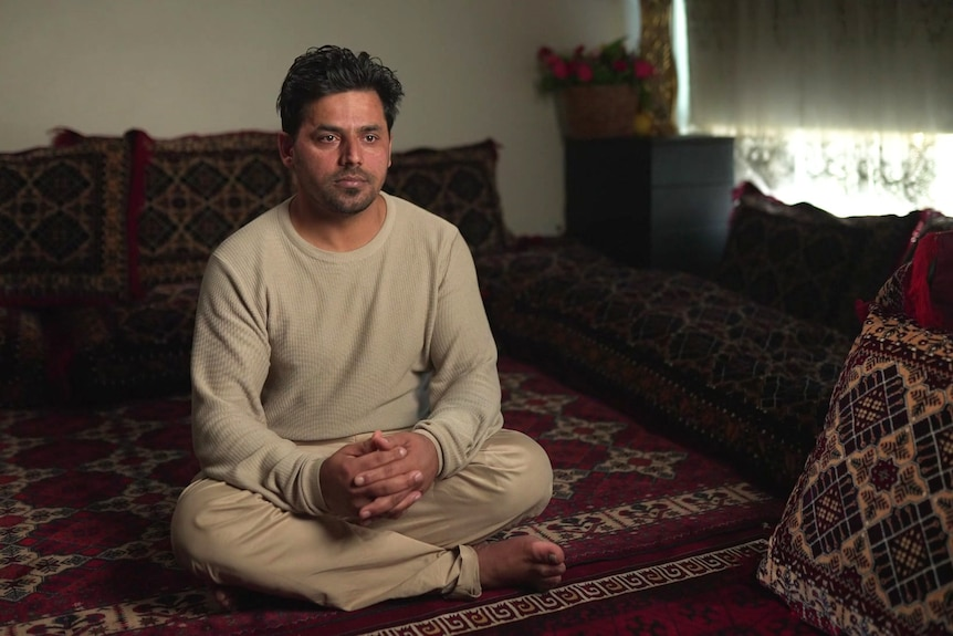 A man wearing a beige top and pants sits on a rug.